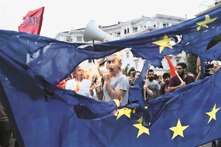 Na cidade portuária de Tessalónica, manifestantes  queimam uma bandeira da União Europeia