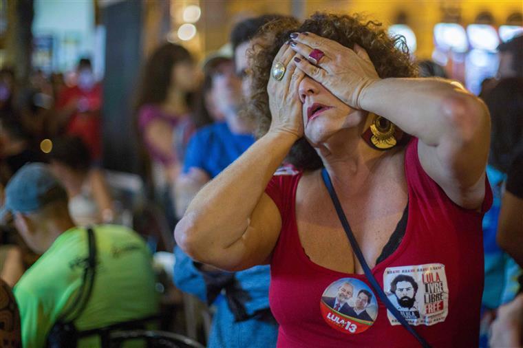 Reação de uma mulher brasileira no momento em que Fernando Haddad, intervém durante a contagem dos votos das eleições gerais num bar na praça São Salvador, bairro de Laranjeiras, na Zona Sul do Rio de Janeiro, Brasil.